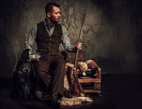 Handsome hunter with a english setter and shotgun in a traditional shooting clothing, sitting on a dark background. Stock Photography