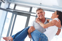 Handsome husband lifting his wife in his arms Royalty Free Stock Image