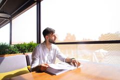 Handsome illustrator watching magazine pictures at table. Young magazine illustrator watching catalog with photos at cafe table. Handsome male person sitting stock photos