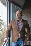 Handsome indian businessman, standing near panoramic window, thinking,