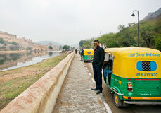 Handsome indian driver stand near the indian moto rickshaw Stock Images