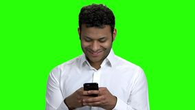 Handsome Indian guy using cell phone. Portrait of attractive businessman using mobile phone on Alpha Channel background stock footage