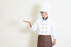 Handsome Indian male chef in uniform holding an empty plate Royalty Free Stock Photography