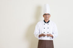 Handsome Indian male chef in uniform holding a plate Royalty Free Stock Photos