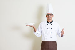 Handsome Indian male chef in uniform holding a plate and thumb u Royalty Free Stock Images