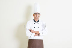 Handsome Indian male chef in uniform with kitchen tools Stock Photography