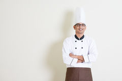 Handsome Indian male chef in uniform. Portrait of handsome Indian male chef in uniform smiling, standing on plain background with shadow, copy space at side royalty free stock photo
