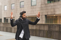 Handsome Indian man listening to music in an urban context Stock Images