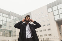 Handsome Indian man listening to music in an urban context Royalty Free Stock Photos