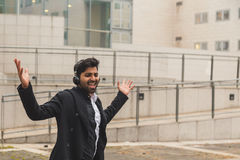 Handsome Indian man listening to music in an urban context Royalty Free Stock Image
