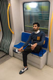 Handsome Indian man posing in a metro car Stock Photo