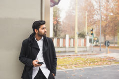 Handsome Indian man texting in an urban context Stock Photo