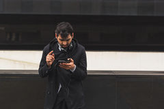 Handsome Indian man texting in an urban context Royalty Free Stock Photos