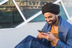 Young Indian man texting in an urban context Royalty Free Stock Photos