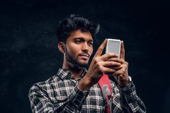 Handsome Indian student with backpack chatting with his friends using a smartphone. Studio photo against a dark textured wall stock photo
