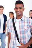 Handsome indian student. Handsome indian high school student with schoolmates on background Royalty Free Stock Images