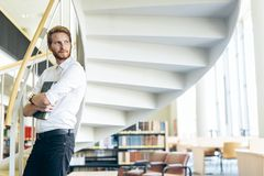 Handsome intelligent guy reading a book in a library stock photography