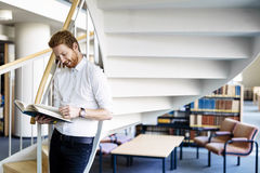 Handsome intelligent guy reading a book in a library Stock Images