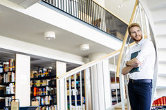 Handsome intelligent guy reading a book in a library Royalty Free Stock Photography
