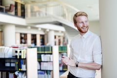 Handsome student smiling in library. Handsome intelligent male student smiling in library Stock Images