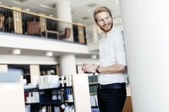 Handsome student smiling in library. Handsome intelligent male student smiling in library Stock Photography