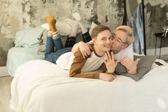 Handsome international homosexual couple who recently married relaxing in bed before night sleep and looking at camera. Showing rings on hands stock image