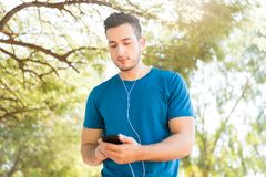 Jogger Listening Music With Earphones And Mobile Phone In Park. Handsome jogger listening music through earphones while using mobile phone in park Stock Image