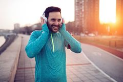 Handsome jogger listening to music. While exercising stock photo