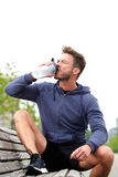 Handsome jogger sitting on bench drinking water Stock Images
