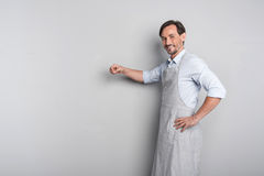 Handsome joyful young man gesturing in an apron Stock Image