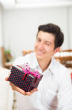 Handsome joyful young man holding Christmas Stock Photos