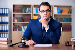 The handsome judge with gavel sitting in courtroom Stock Image