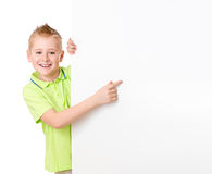 Handsome kid boy pointing to blank advertisement banner royalty free stock photos