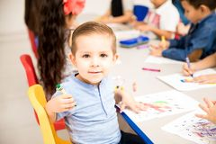Cute little boy coloring with crayons. Handsome kindergarten male student doing some coloring with crayons in the classroom and having a good time Royalty Free Stock Photos