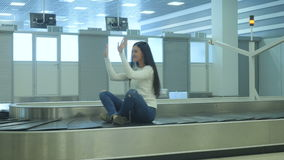Handsome lady sits at the luggage conveyor and moves along. The action takes place at the arriving hall of the airport at the baggage claim desk. Handsome young stock video footage