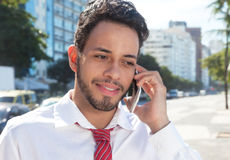 Handsome latin businessman at phone in the city Royalty Free Stock Photos
