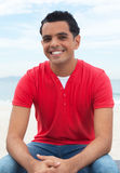 Handsome latin guy at beach looking at camera Stock Photo