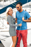 Handsome latin man and blond woman standing on yacht Stock Photography