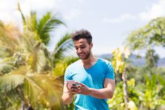 Handsome Latin Man Communicating Online Use Cell Smart Phone Ountdoors Over Tropical Forest And Blue Sky, Portrait Of Stock Image