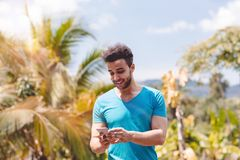 Handsome Latin Man Messaging With Cell Smart Phone Over Tropical Forest Background, Portrait Of Young Guy Chatting Stock Photo
