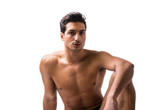 Handsome latin young man sitting naked on floor,. A handsome latin young man sitting naked on floor, wearing only underwear. Muscular build Royalty Free Stock Image