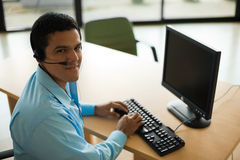 Handsome Latino Customer Service Representative. A handsome latino customer service representative turns his head and looks over his shoulder into the camera Stock Photography
