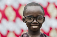 Handsome little African boy smiling outdoors with big black glasses on. Young african boy in eyeglasses looking at camera Royalty Free Stock Photo