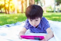 Handsome little boy is addicted social media or online game by always playing on tablet all day and every time. Lovely kid is atte royalty free stock image