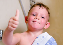 Handsome little boy with a big happy smile. Giving a thumbs up gesture of approval as he stands draped in a towel in his bath with wet hair, close up of his Royalty Free Stock Photos
