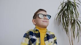 A handsome little boy with blue eyes wears sunglasses and looks aside. In the room, on a white background stock footage