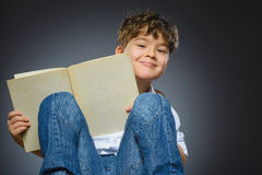 Handsome little boy with book smiling isolated on gray background stock photography