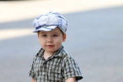 Handsome little boy in cap stands on asphalt and looks away Stock Images