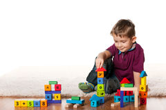Handsome little boy on the floor with toys Stock Images
