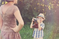 Handsome little boy with retro camera and girl model stock photography